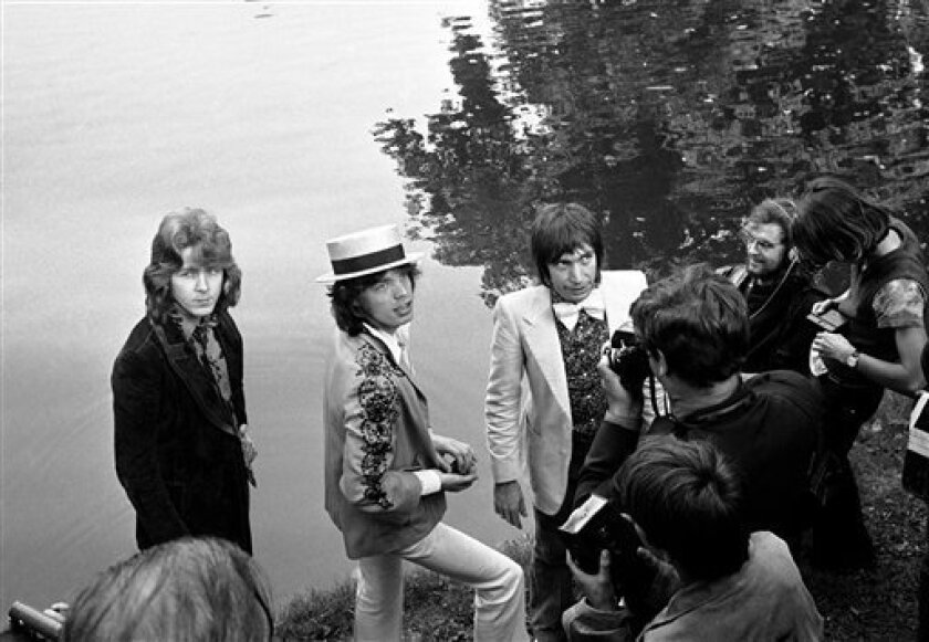 """FILE - This Sept. 22 1970 file photo shows Mick Jagger, center, lead singer of The Rolling Stones pop music group, with a straw hat, as he and guitarist Mick Taylor and drummer Charlie Watts, right in bow tie, pose during a press conference at the Bois de Boulogne in Paris, France . In 1972, The Rolling Stones controversially moved to the south of France to escape onerous British taxes. Though it caused a stink at the time, it spawned one of the group's most seminal albums, """"Exile on Main St."""" The title is a reference to their tax-dodging. (AP Photo, Cardenas, File)"""