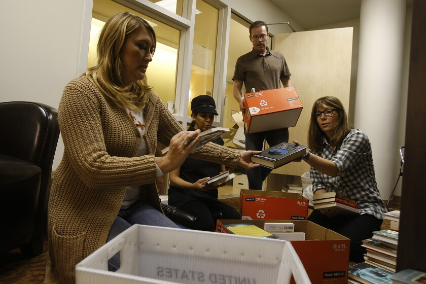 Volunteers are seen preparing donated books for the library in the Downtown Women's Center.