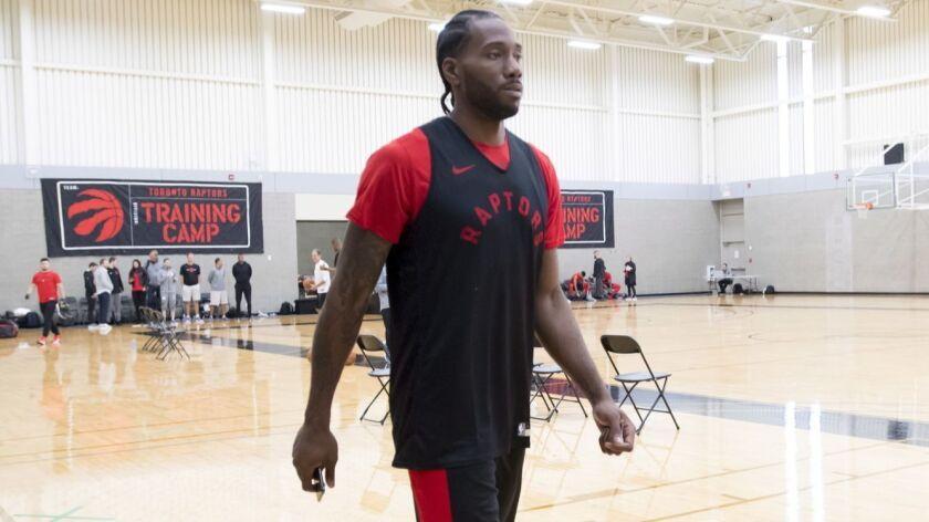 Toronto Raptors' Kawhi Leonard walks on the court during NBA basketball practice, Tuesday, Sept. 25,