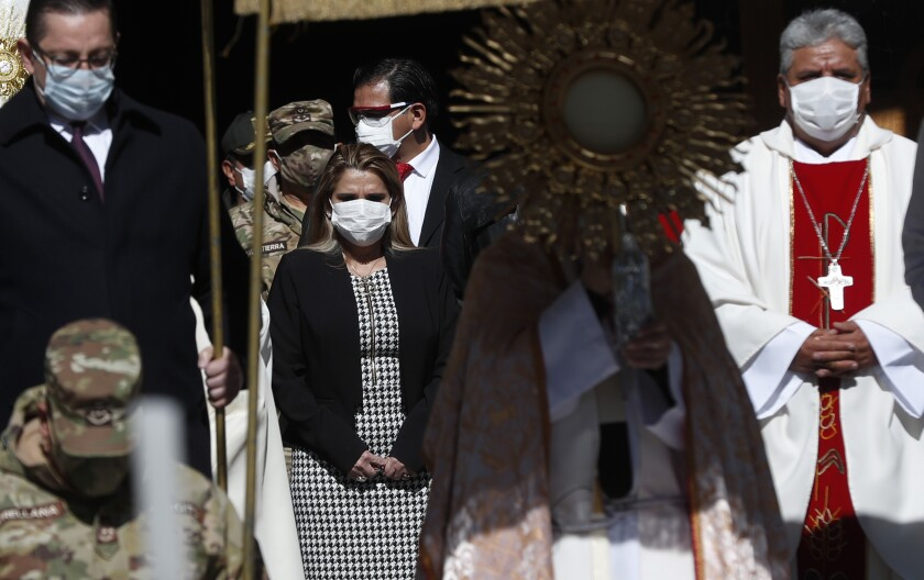 Bolivia's interim President Jeanine Anez, center left, wearing a face mask as a measure to help curb the spread of the new coronavirus, takes part in a procession marking Corpus Christi, which commemorates the biblical transubstantiation of bread and wine into the body and blood of Christ, amid the new coronavirus pandemic in La Paz, Bolivia, Thursday, June 11, 2020. Due to the pandemic the religious holiday was arranged to encourage faithful to stay home offering an online Mass and the procession to be escorted by members of the military. (AP Photo/Juan Karita)