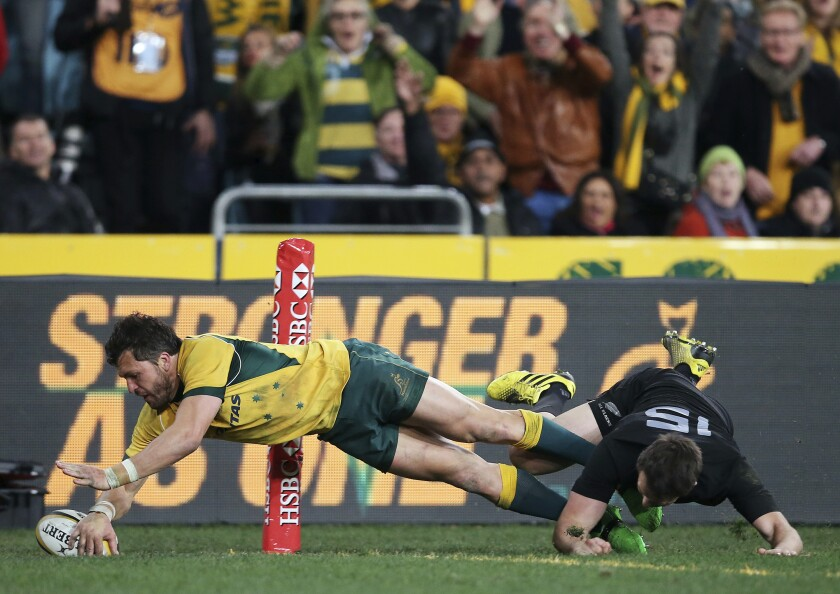 FILE - In this Aug. 8, 2015, file photo, Australia's Adam Ashley-Cooper, left, dives past New Zealand's Ben Smith to score a try during their Rugby Championship match in Sydney. Australia is set to host the Rugby Championship in November and December after a late change of mind by governing body SANZAAR, Friday, Sept. 11, 2020. (AP Photo/Rick Rycroft, File)
