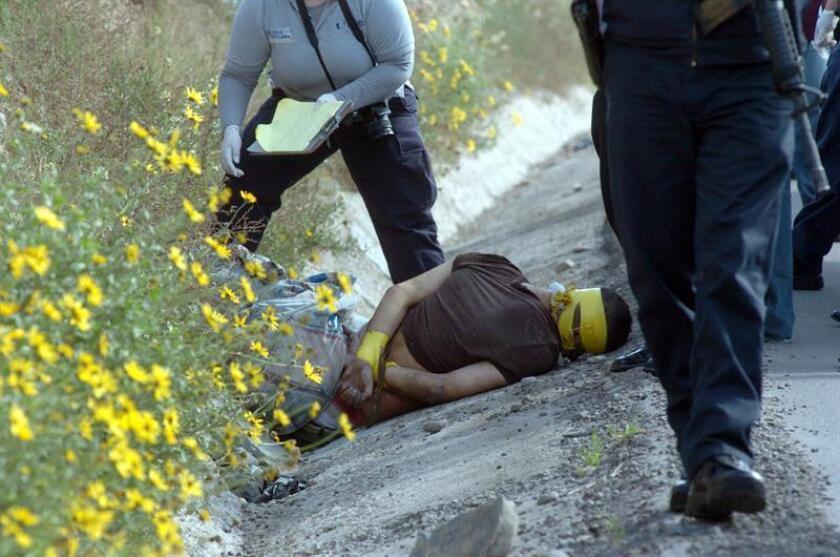Policías federales caminan el 3 de marzo de 2009, en el sitio donde fue hallado el cuerpo de un hombre con el rostro cubierto con cinta adhesiva, que se suma a otros tres hombres más decapitados en Tijuana, México, según reportes de la Procuraduría General de Justicia (PGJE). EFE/Archivo