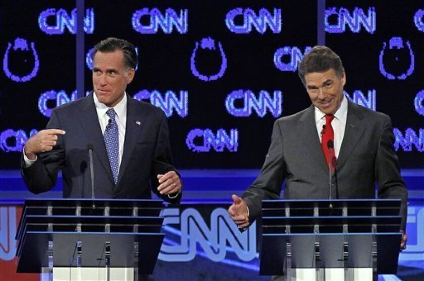 FILE - In this Oct. 18, 2011, file photo Republican presidential candidates Mitt Romney and Rick Perry, right, spar during a Republican presidential debate in Las Vegas. Perry, still nursing wounds from his failed presidential campaign, did himself a world of good with his self-deprecating jokes at