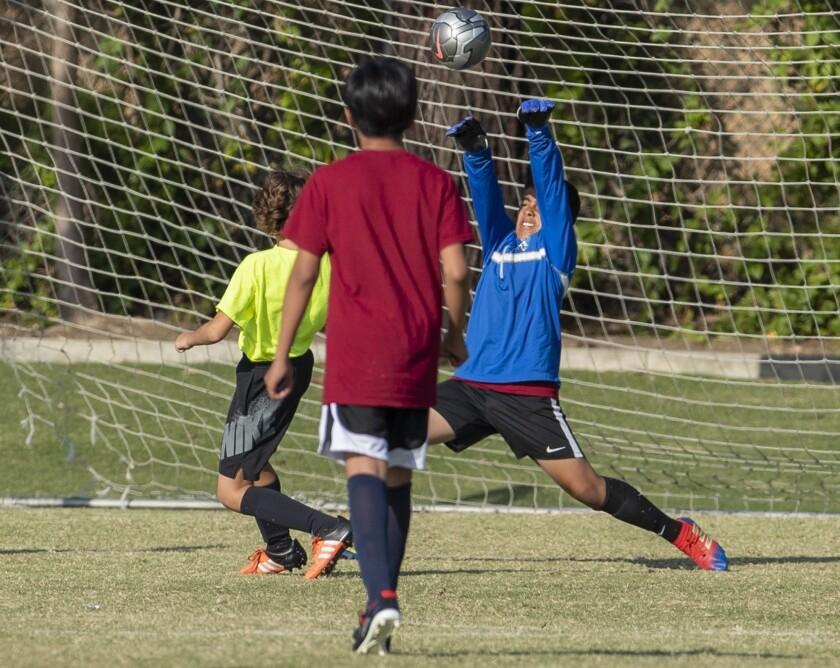 Costa Mesa Pomona's Joel Perez blocks a shot against Newport Coast's Grant Davidson in a boys? fifth