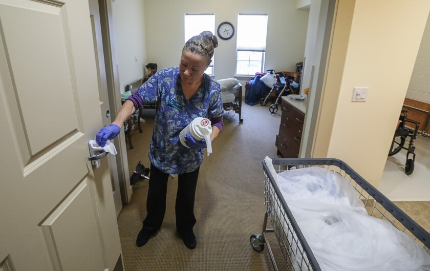 Mina Montano, an environmental aide at St. Paul's Plaza, uses disinfectant wipes to clean high-touch areas in March.