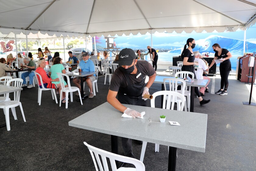 Arturo Guzman cleans a table in the outdoor dining area at Cappy's Cafe in Newport Beach in July.