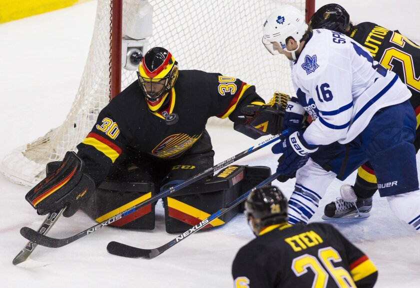 Vancouver Canucks goaltender Ryan Miller (30) makes a save against Toronto Maple Leafs' Nick Spaling (16) during second-period NHL hockey game action in Vancouver, British Columbia, Saturday, Feb. 13, 2016. (Ben Nelms/The Canadian Press via AP) MANDATORY CREDIT