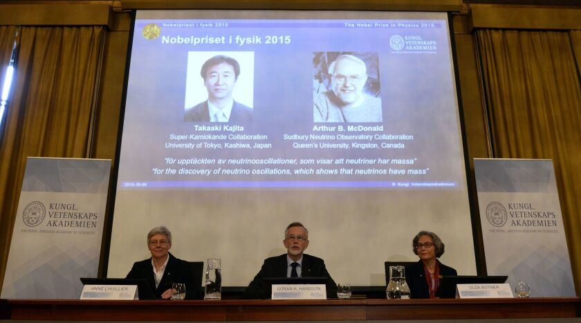 Portraits of Takaaki Kajita, left, and Arthur B. McDonald are projected behind Nobel Committee for Physics members at a news conference about the two prizewinners.
