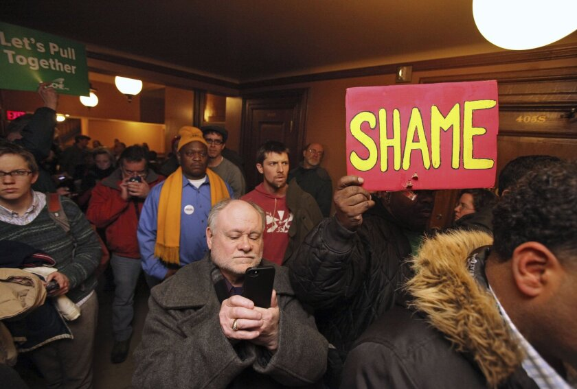 A crowd protests outside the doors of a hearing that was cut short for a right-to-work bill at the Wisconsin Capitol in Madison.