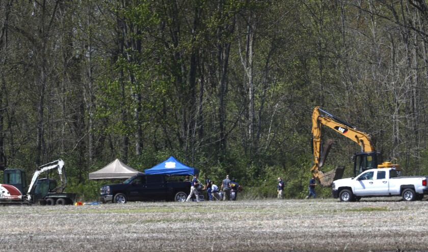 Authorities work near a rural wooded area in Macomb Township, Mich., Tuesday, May 8, 2018.