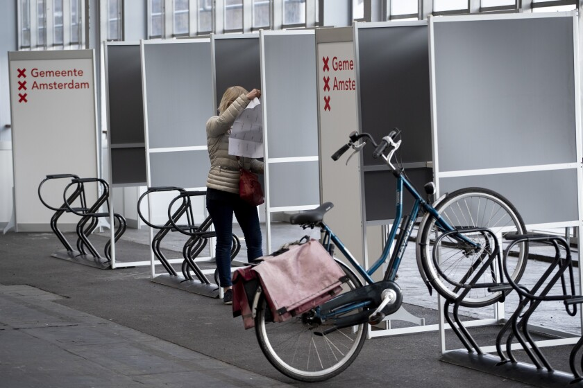 A woman prepares to cast her ballot in ride through polling station for bicycles in Amsterdam, Netherlands, Monday, March 15, 2021. Polling stations opened across the Netherlands early Monday in a general election that has been spread over three days to allow people to vote safely during the coronavirus pandemic. (AP Photo/Peter Dejong)