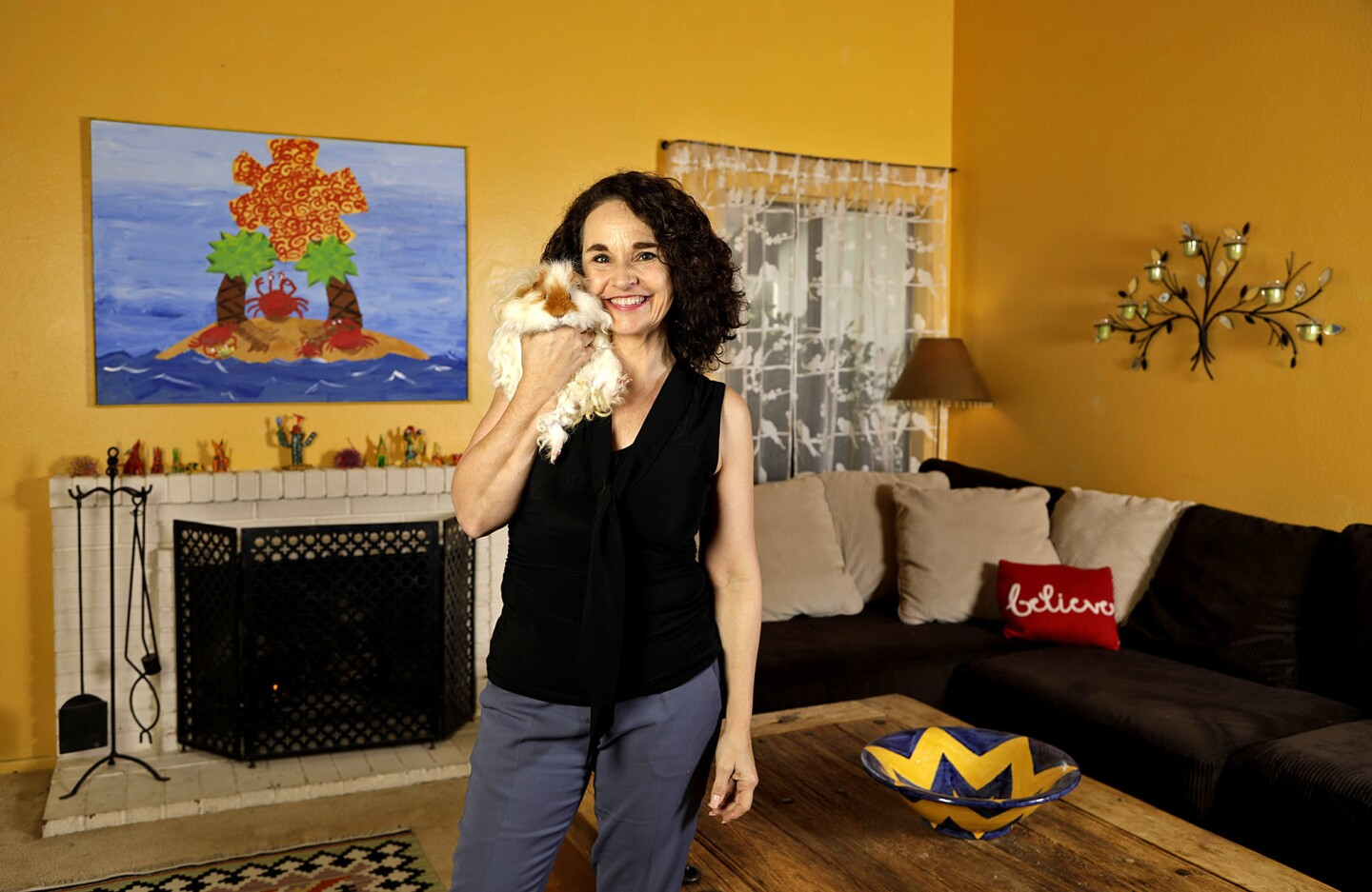 Actress Diane Franklin and her pet guinea pig in her sunny yellow living room.