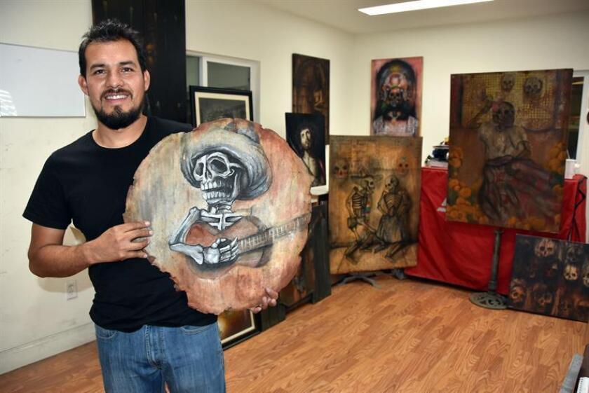 """Fotografía del 21 de octubre de 2018, donde aparece el pintor mexicano Jesús Molina mientras muestra su obra titulada """"El comal"""" en su taller en la ciudad de San Fernando ubicada al noroeste del Condado de Los Ángeles en California (EE.UU.). EFE"""