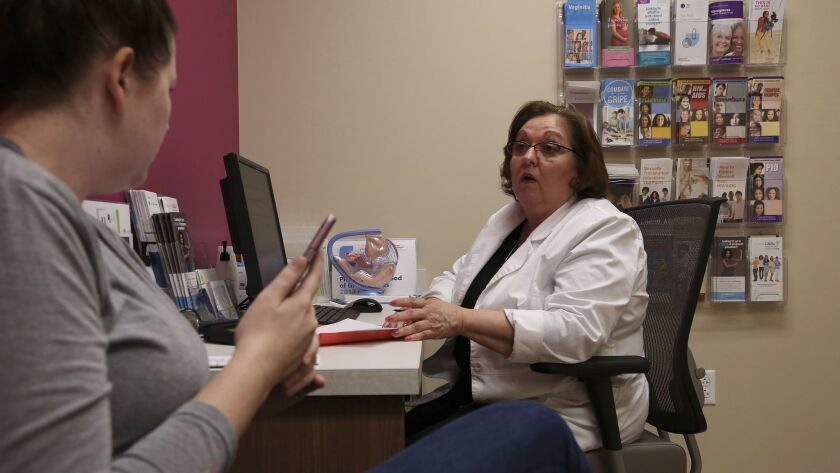 Vivian Bigelow, a nurse practitioner at a Planned Parenthood health center in Plano, Texas, consults