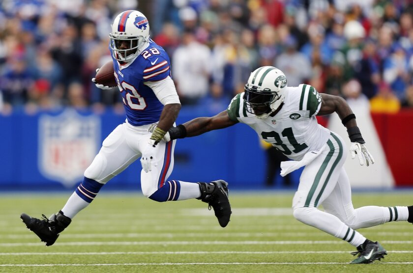 Buffalo Bills running back C.J. Spiller (28) eludes New York Jets cornerback Antonio Cromartie (31) during the first half of an NFL football game on Sunday, Nov. 17, 2013, in Orchard Park, N.Y. (AP Photo/Gary Wiepert)