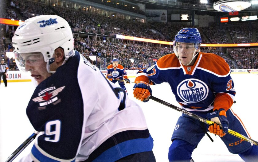 Winnipeg Jets' Andrew Copp (9) is chased by Edmonton Oilers' Connor McDavid (97) during the first period of an NHL hockey game Saturday, Feb. 13, 2016, in Edmonton, Alberta. (Jason Franson/The Canadian Press via AP)
