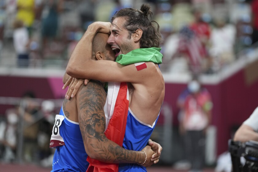 High jump gold medalist Gianmarco Tamberi, right, of Italy, congratulates compatriot Lamont Marcell Jacobs, after he won the final of the men's 100-meters at the 2020 Summer Olympics, Sunday, Aug. 1, 2021, in Tokyo. (AP Photo/Matthias Schrader)