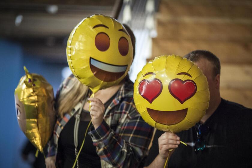 Attendees at the Emojicon launch party pose for pictures with emoji balloons.