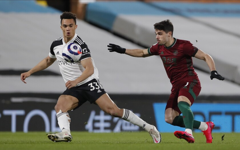 Fulham's Antonee Robinson, left, and Wolverhampton Wanderers' Pedro Neto challenge for the ball during the English Premier League soccer match between Fulham and Wolverhampton Wanderers at Craven Cottage stadium in London, England, Friday, April 9, 2021.(Andrew Couldridge/Pool via AP)