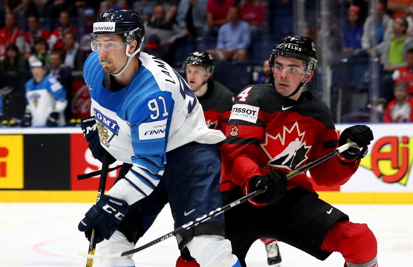 Canada's Dante Fabbro, right, defends against Finland's Juha Lammikko during the 2019 IIHF championship game.
