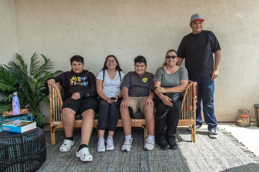 Nicolas, Natalia, Adrian, Clara and Francisco take in the changes in their new backyard on their outdoor couch.