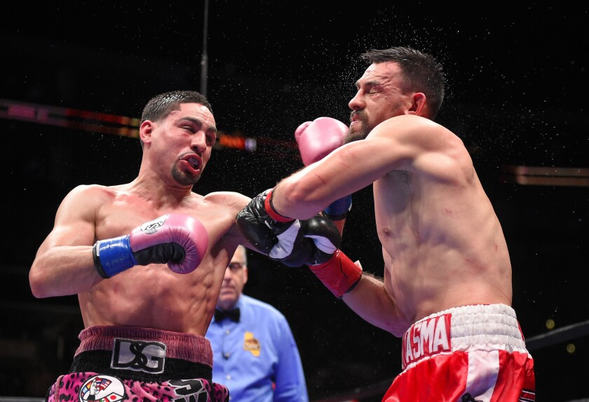 Danny Garcia, left, and Robert Guerrero trade punches in the middle of the ring during their WBC welterweight title fight on Jan. 23.