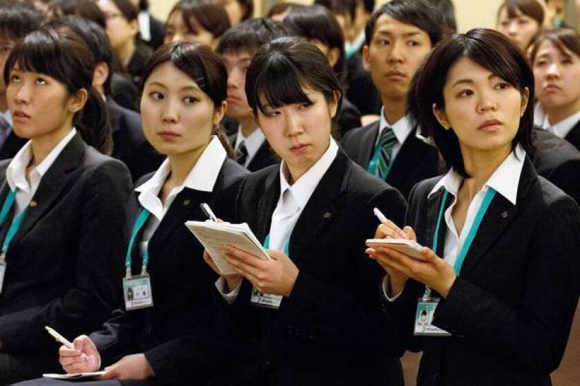 Japan aims to raise women's labor participation to the world's highest level and is urging firms to promote them. Above, a meeting is held for new Seven & I Holdings workers in Tokyo in March.
