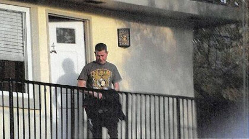 Alex Taylor is seen wearing a gold DEA-style badge around his neck outside a San Jose residence on March 1. Authorities say the man has been impersonating an agent.