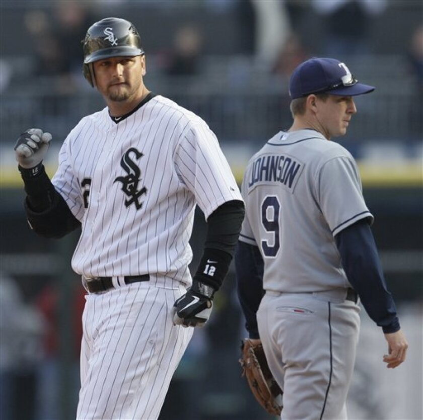 Chicago White Sox's A.J. Pierzynski, left, celebrates after hitting a two-run double, as Tampa Bay Rays shortstop Elliot Johnson looks to the dugout during the seventh inning of a baseball game in Chicago, Saturday, April 9, 2011. The White Sox won 4-2. (AP Photo/Nam Y. Huh)