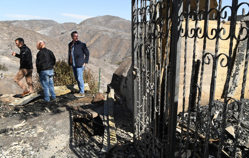 Los Angeles Mayor Eric Garcetti, left, City Councilman Mike Bonin and California Gov. Gavin Newsom view a burned home on Tigertail Road in Brentwood on Tuesday.