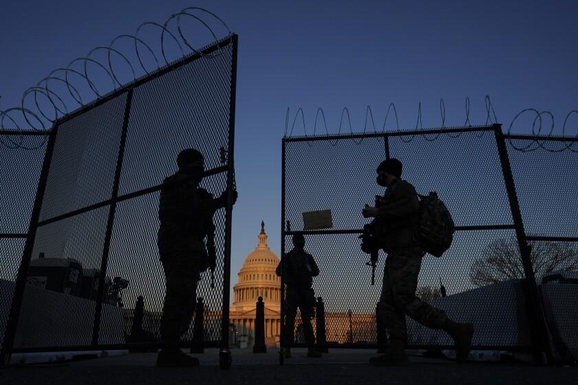 Miembros de la Guardia Nacional abren un portón del cerco que rodea el Congreso