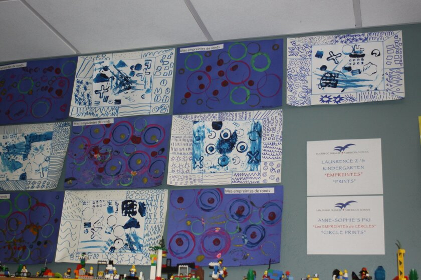 """Along the wall, are examples of """"empreintes"""" (prints) and """"les empreintes des cercles"""" (circle prints) from Laurence Zede-Humbert's kindergarten class and Anne Sophie Nguyen Tregouet's pre-elementary class."""