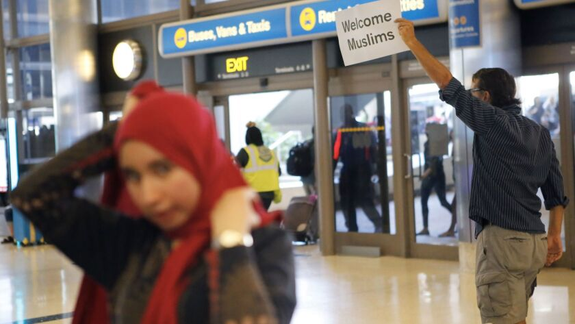A protester at LAX holds a sign welcoming Muslims to the United States on Thursday.