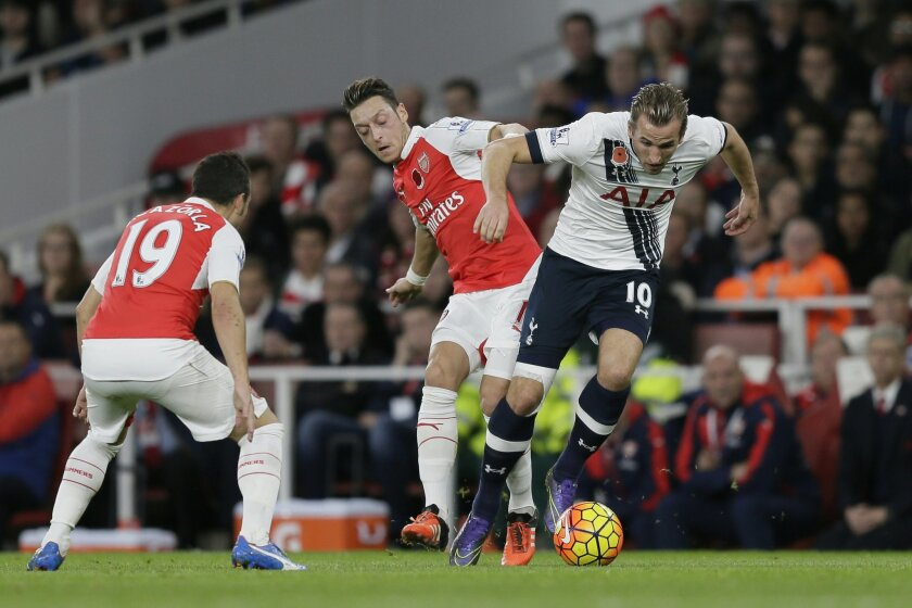Arsenal's Mesut Ozil, centre, competes for the ball with Tottenham's Harry Kane during the English Premier League soccer match between Arsenal and Tottenham Hotspur at the Emirates Stadium in London, Sunday Nov. 8, 2015. (AP Photo/Tim Ireland)