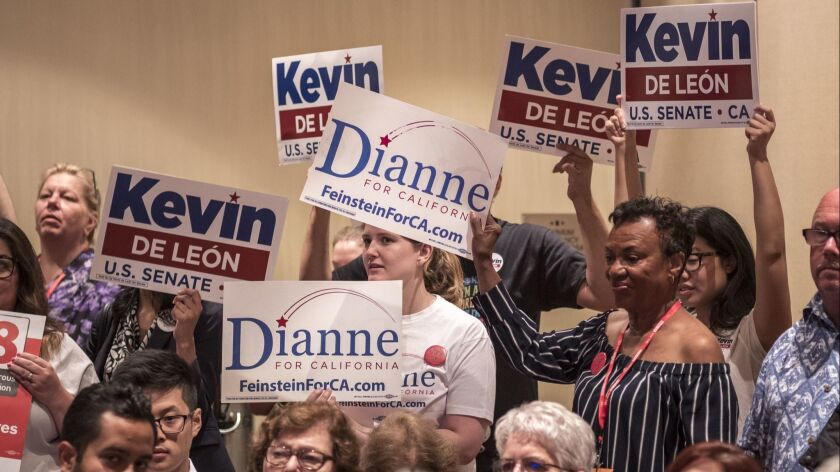 Supporters of Kevin de León and Dianne Feinstein hold signs during a meeting of the state Democratic Party's executive board in Oakland on July 14.