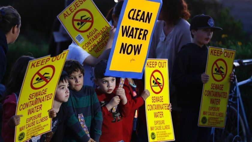 Children hold signs before the start of an International Boundary and Water Commission meeting on about 143 million gallons of sewage spilled in the Tijuana river.