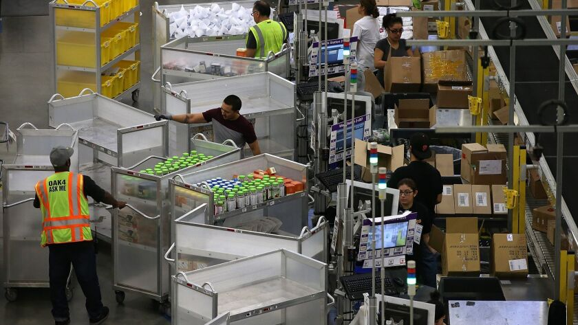 Amazon.com workers pack orders at an Amazon fulfillment center in Tracy, Calif. Amazon said it will boost its minimum pay for all U.S. workers to $15 an hour.