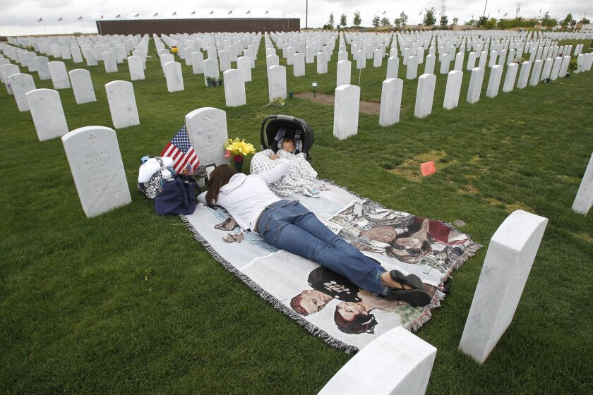 Jenn Budenz lies on a blanket with her 2-month-old son AJ as they visit the grave of her husband and father of her child Major Andrew Budenz, who was a Marine C-130 pilot in Iraq and Afghanistan, at the Miramar National Cemetery in San Diego on Thursday. Andrew Budenz was killed last September in