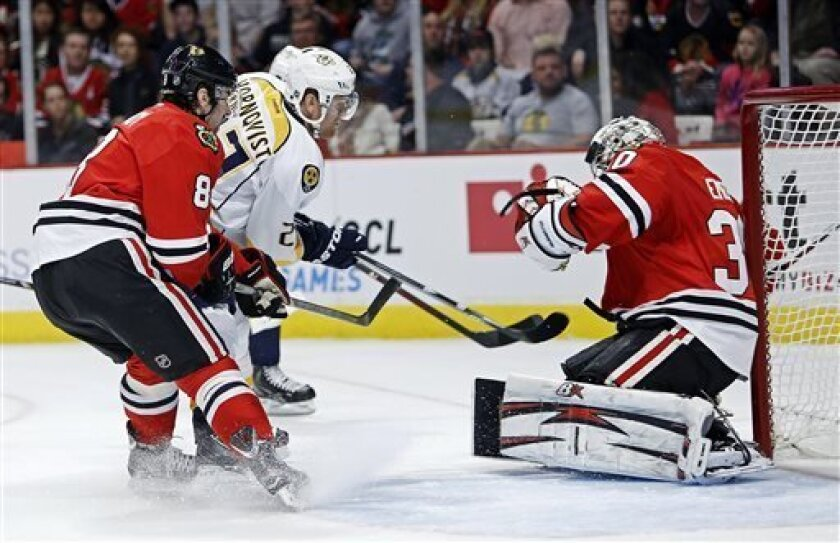 Chicago Blackhawks goalie Ray Emery makes a save on Nashville Predators' Patric Hornqvist during the first period as Blackhawks defenseman Nick Leddy watches for a rebound in an NHL hockey game in Chicago, Sunday, April 7, 2013. (AP Photo/Charles Cherney)