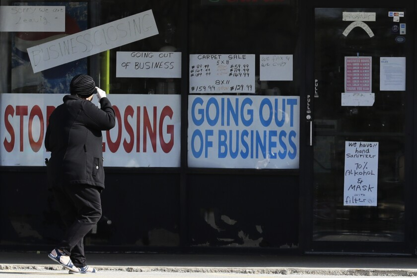 "A woman passes a ""store closing"" sign."