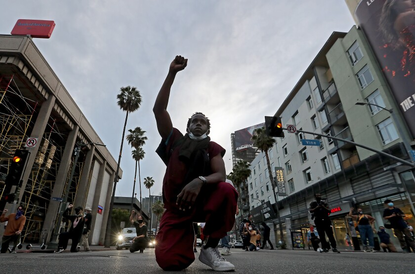 A man kneels in the street and holds his fist up.