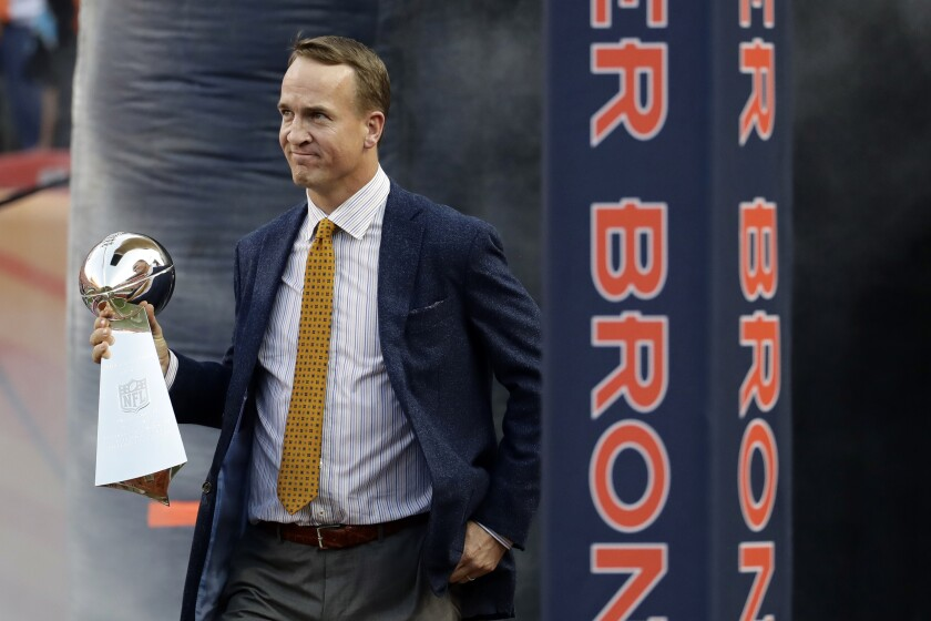 FILE - Former Denver Broncos quarterback Peyton Manning carries the Vince Lombardi Trophy from Super Bowl 50 onto the field prior to an NFL football game against the Carolina Panthers in Denver, in this Thursday, Sept. 8, 2016, filer photo. The only five-time league MVP, Manning quarterbacked Indianapolis to two Super Bowls, winning one, and then took Denver to two more, winning one. Peyton Manning is one of four first-year-eligible 2021 finalists for the Pro Football Hall of Fame, to be announced Saturday, Feb. 6, 2021. (AP Photo/Jack Dempsey, File)