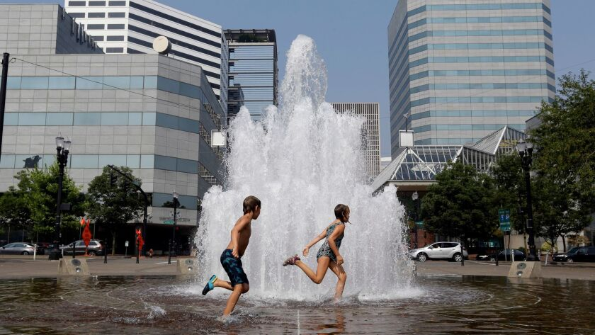 Langstrom Kalstrom, left, and Violet Dashney run through the Salmon Street Springs fountain in Portland, Ore., as the city endured triple-digit heat.