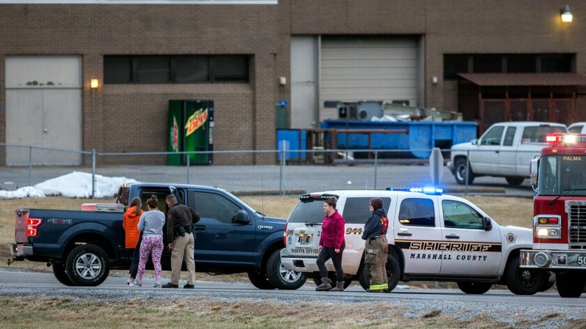 Marshall County High School students are escorted to retrieve their vehicles by emergency responders after a deadly shooting at the school in Benton, Ky., on Tuesday.