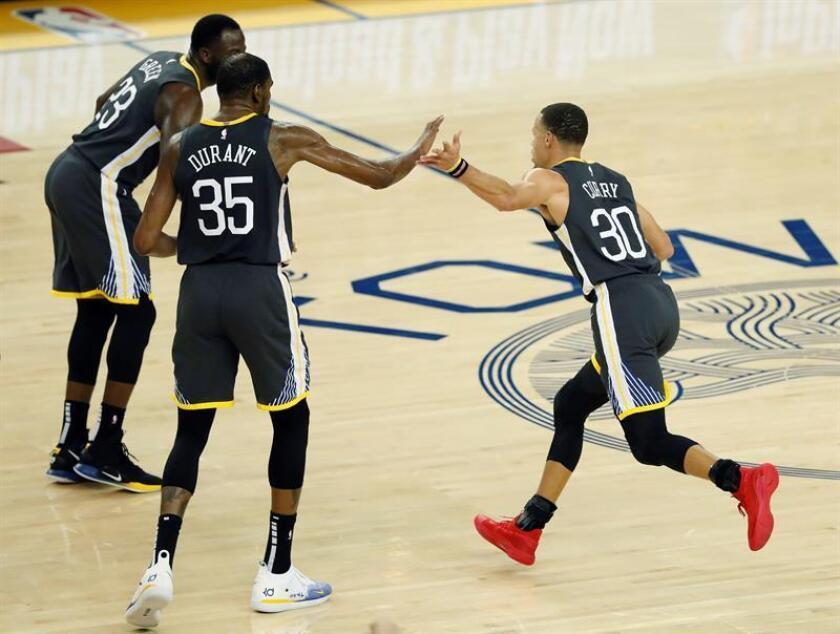 El base de los Warriors de Golden States Stephen Curry (d) celebra con compañeros tras marcar un triple durante el partido de la NBA entre los Warriors de Golden State y los Pelicans de Nueva Orleans en el Oracle Arena en Oakland, California, Estados Unidos, el 16 de enero de 2019. EFE