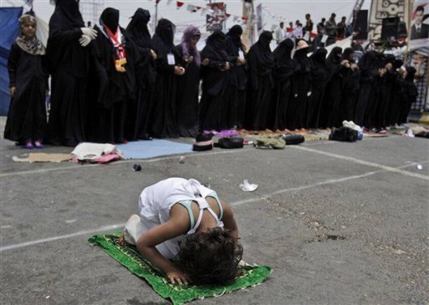 A Yemeni girl, prays in front of female anti-government protestors attending noon prayers, during a demonstration demanding the resignation of President Ali Abdullah Saleh, in Sanaa, Yemen, Thursday, June 23, 2011. Nearly 60 suspected al-Qaida militants have tunneled their way out of a Yemeni prison in the lawless south, deepening the chaos of a nation where protesters are trying to topple the autocratic regime. (AP Photo/Hani Mohammed)