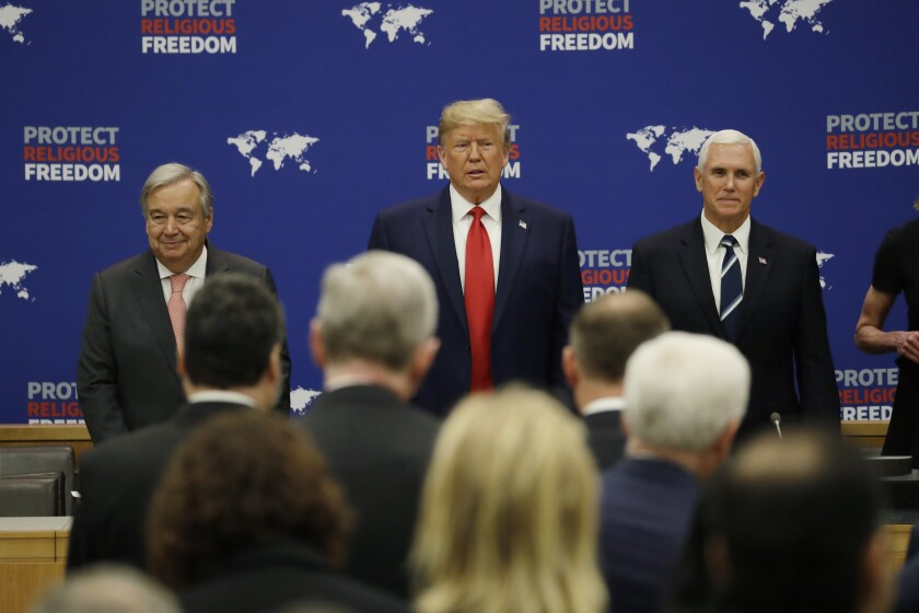 President Trump arrives at an event on religious freedom during the U.N. General Assembly on Monday. He is flanked by U.N. Secretary-General Antonio Guterres, left, and Vice President Mike Pence.