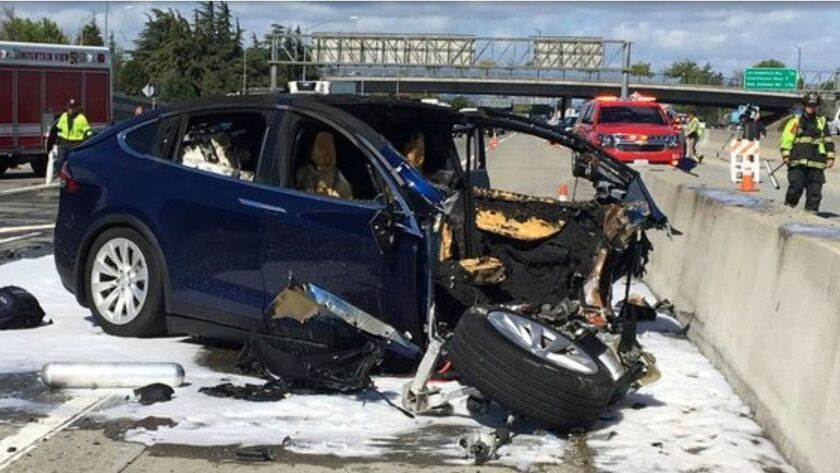 Too soon for Autopilot? Emergency personnel on the scene of a March 23, 2018, fatal crash involving a Tesla operating on Autopilot in Mountain View, Calif.