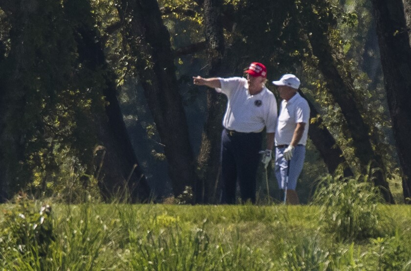 President Donald Trump and Sen. Lindsey Graham, R-S.C., right, play golf at Trump National Golf Club in Sterling, Va., as seen from the other side of the Potomac River in Darnestown, Md., Saturday, July 18, 2020. (AP Photo/Manuel Balce Ceneta)