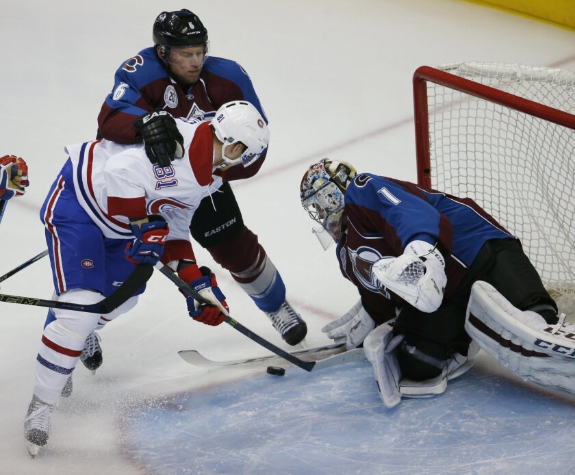 Montreal Canadiens center Lars Eller, left, front, of Denmark, is held by Colorado Avalanche defenseman Erik Johnson, back left, while trying to shoot the puck at goalie Semyon Varlamov, of Russia, in the first period of an NHL hockey game Wednesday, Feb. 17, 2016, in Denver. (AP Photo/David Zalubo